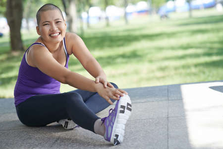Vietnamese bald woman doing exercising outdoors Stock Photo
