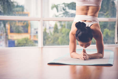 headstand: Vietnamese woman performing supported headstand Stock Photo