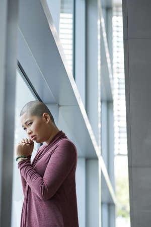 ウィンドウにがん立っているから苦しんでいるアジア女性 写真素材