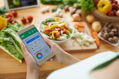 Vrouw die calorietellertoepassing op haar smartphone gebruiken Stockfoto