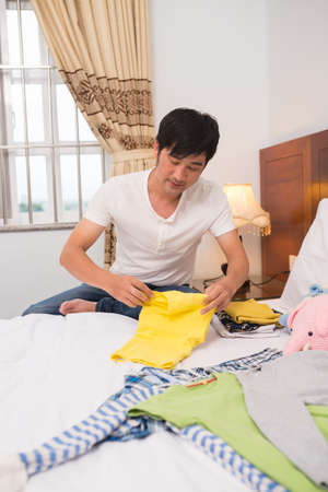 Caring dad folding childrens clothes