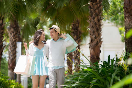 familia abrazo: Cheerful Asian couple with paper bags walking outdoors