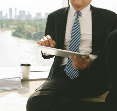 personas leyendo: Cropped image of businessman using application on digital tablet