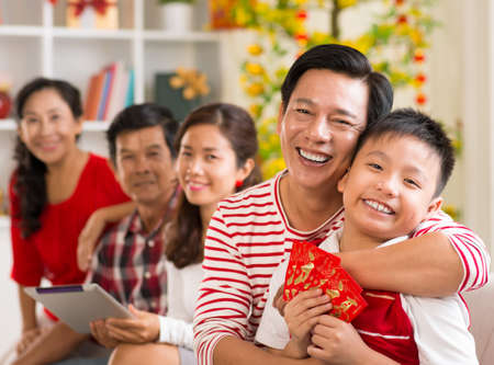 Happy father hugging his son who is holding lucky money envelopes Stock Photo
