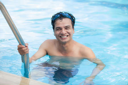 old asian: Happy man climbing out of swimming pool