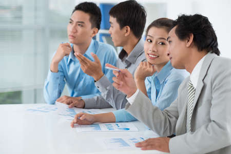 office presentation: Business colleagues talking when listening to presentation Stock Photo