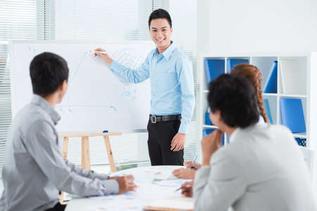 office presentation: Smiling young businessman conducting presentation in front of his colleagues