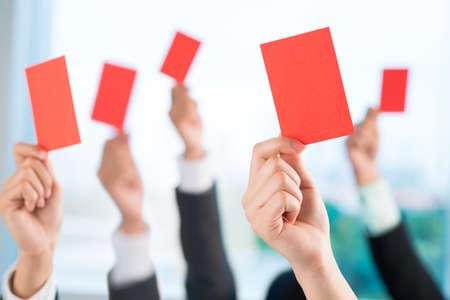 Manos de los hombres de negocios que muestran tarjetas rojas para condenar la mala práctica empresarial Foto de archivo - 73296529