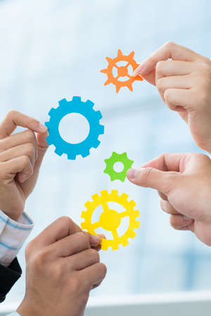 business gears: Hands of business colleagues holding gears to make up powerful mechanism