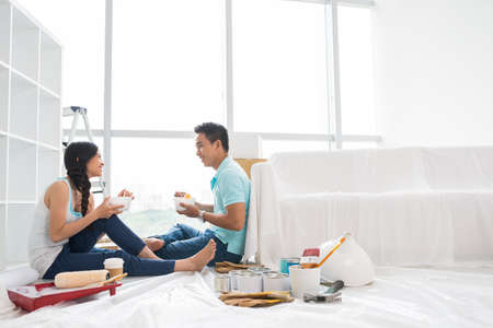 Asian couple talking and eating instant noodle after moving to new house