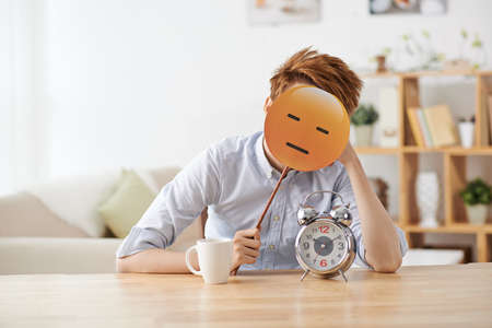 Man sitting at the table with alarm clock and covering his face with emoji Stock Photo