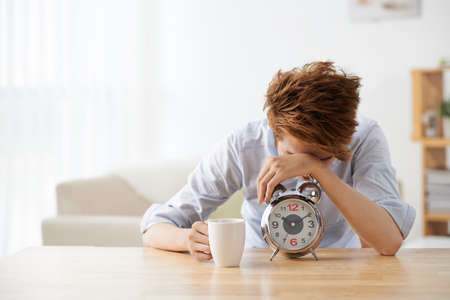 slumber: Sleepy young man with alarm clock sitting at the table