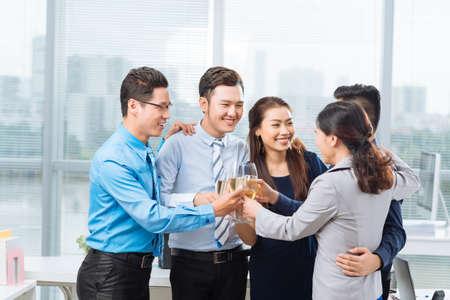 personas abrazadas: Abrazando a la gente de negocios que tuestan para celebrar el éxito