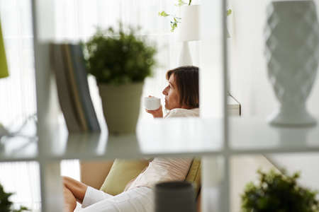 melancholy: Pensive woman enjoying cup of tea at home Stock Photo