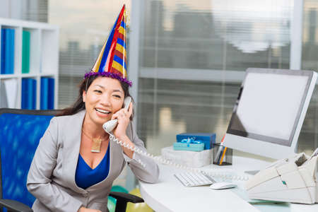 telephone call: Middle-aged business lady receiving congrats on the telephone
