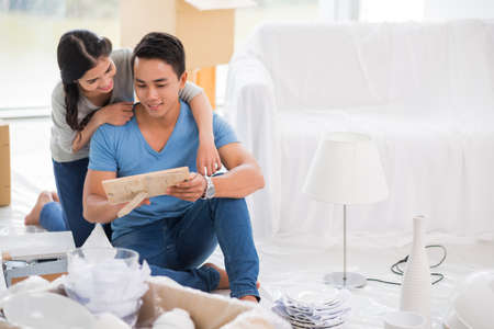 couples hug: Young couple found old photo when unpacking their belongings