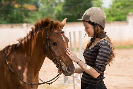 Happy Asian girl in helmet stroking pony