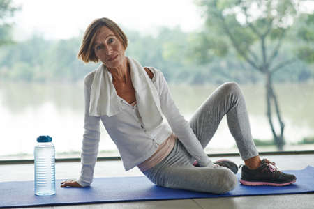 Senior woman performing exercises on the mat Imagens