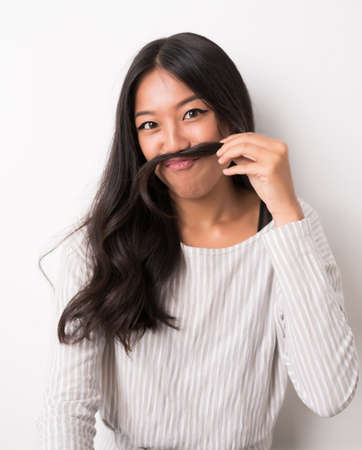 fake smile: Funny young woman making moustache out of her hair