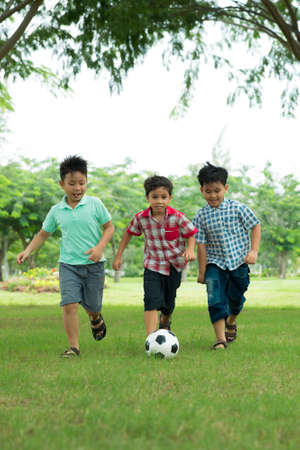 Opgewekte schooljongens die voetbal in het park spelen Stockfoto