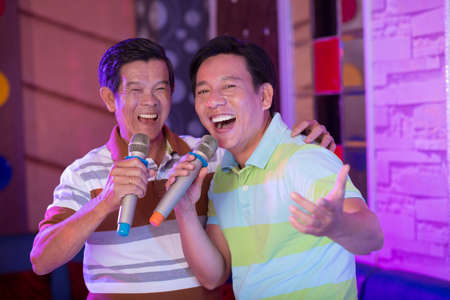 Portrait of two Asian men enjoying their time in karaoke Stock Photo