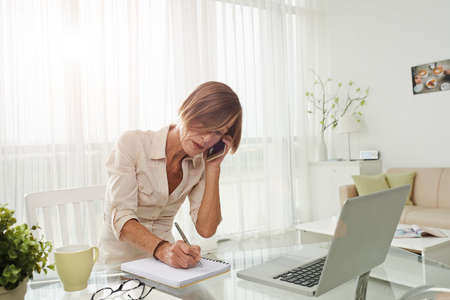 Middle-aged business lady talking on the phone and making notes in her home-office