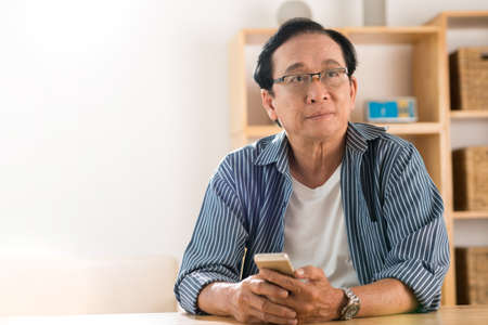 Portrait of pensive man with a smartphone trying to remember telephone number