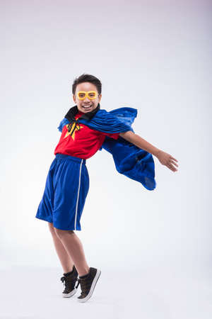 Cheerful boy wearing superhero costume with a cape Stock Photo