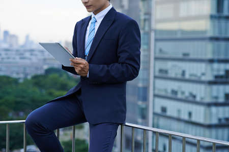 Young business executive working on digital tablet when standing rooftop of skyscraper