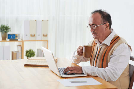 Mature businessman drinking coffee and checking e-mail on his laptop Stock Photo