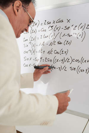Mature teacher rewriting formulas in the digital tablet on the whiteboard Stock Photo