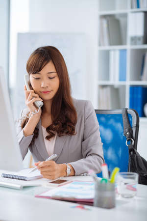 telephone call: Pretty Japanese manager talking on the phone and making notes
