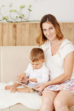 woman tablet: Woman teaching her little son how to use digital tablet Stock Photo