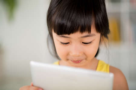 Close-up image of cute little girl using application on digital tablet in her hands Stock Photo