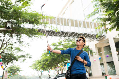 Excited young man using selfie stick to make a perfect photo