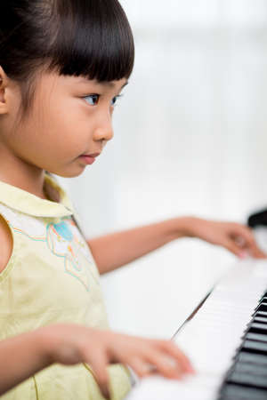 prodigy: Portrait of concentrated Asian girl playing the piano Stock Photo