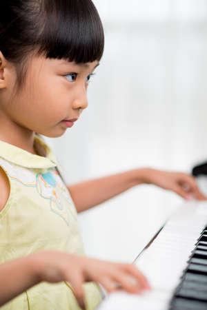 Prodigy: Portret dziewczyny skoncentrowanego azjatyckiej gry na fortepianie