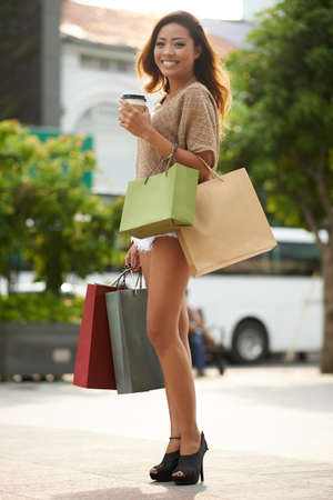 Full-length portrait of cheerful sexy woman with many shopping bags standing outdoors Stock Photo