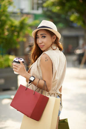 Fashionable young woman with shopping bags and cup of coffee smiling at camera