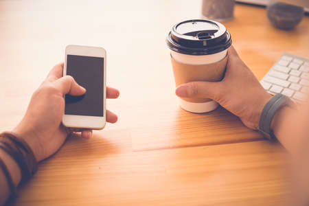 guy person: Guy with smartphone drinking take-out coffee and checking out the news feed, first person view Stock Photo