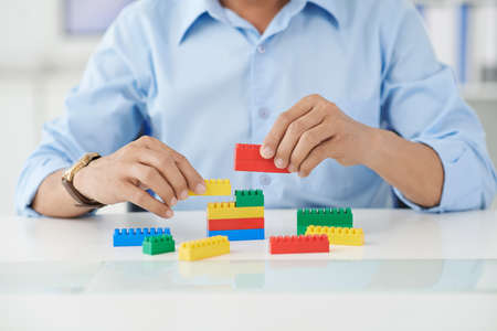 Businessman connecting lego details at his place of work Stock Photo
