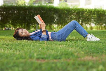 Pretty Asian student lying on grass with her favorite book and smiling at the camera