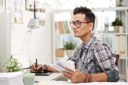 Portrait of concentrated designer drawing on graphic tablet Stock Photo