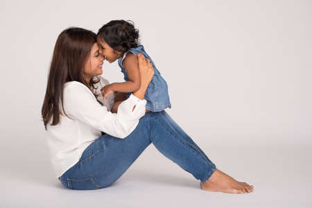 familia abrazo: Little girl biting her nose of her mother