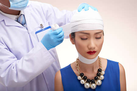 Fashionable woman having her head bandage removed at surgeon