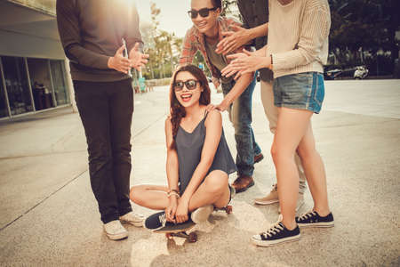Teenage friends giving a ride to their girlfriend on skateboard