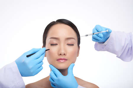 mujer bonita: Hands of medical workers preparing woman for facial plastic surgery