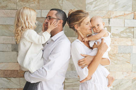 Parenthood concept: happy father and mother holding daughters in their arms Stock Photo