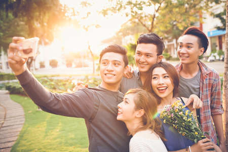 asian group: Cheerful teenage friends taking selfie against sunset Stock Photo