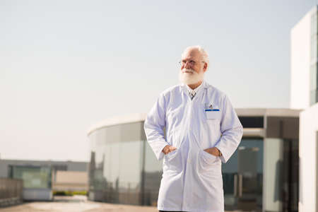Senior man standing in lab coat at his research center